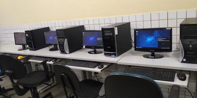 Imagem mostrando o Regata OS instalado em computadores no laboratório de informática.