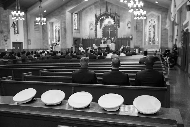 Servicemen's hats behind the pews in the church at Jin and Christopher's wedding