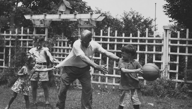 Dr. James Naismith plays basketball with his grandchildren in the backyard. Baskets and Ladders. marchmatron.com