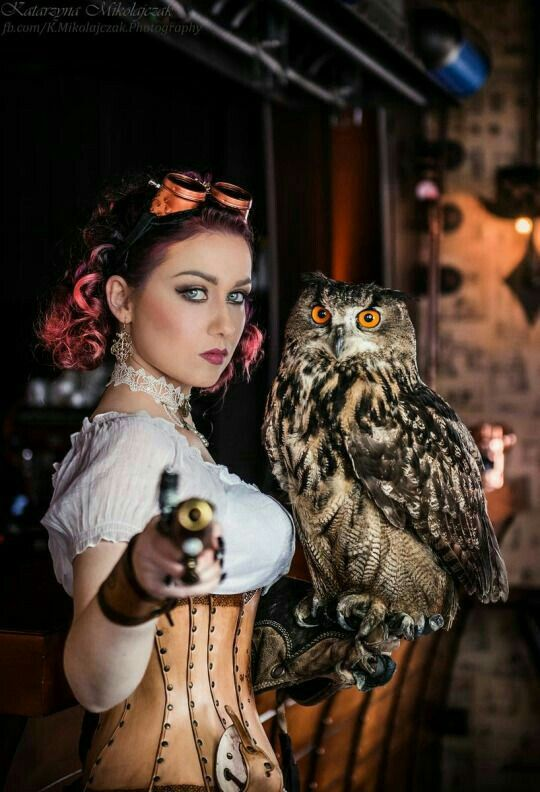 Women in steampunk clothing (goggles, leather corset) holding an owl and wearing steampunk jewelry. Women's steampunk fashion and costumes