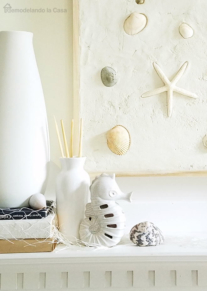 Superb sea shells wall art on mantel with white vase and wooden fish