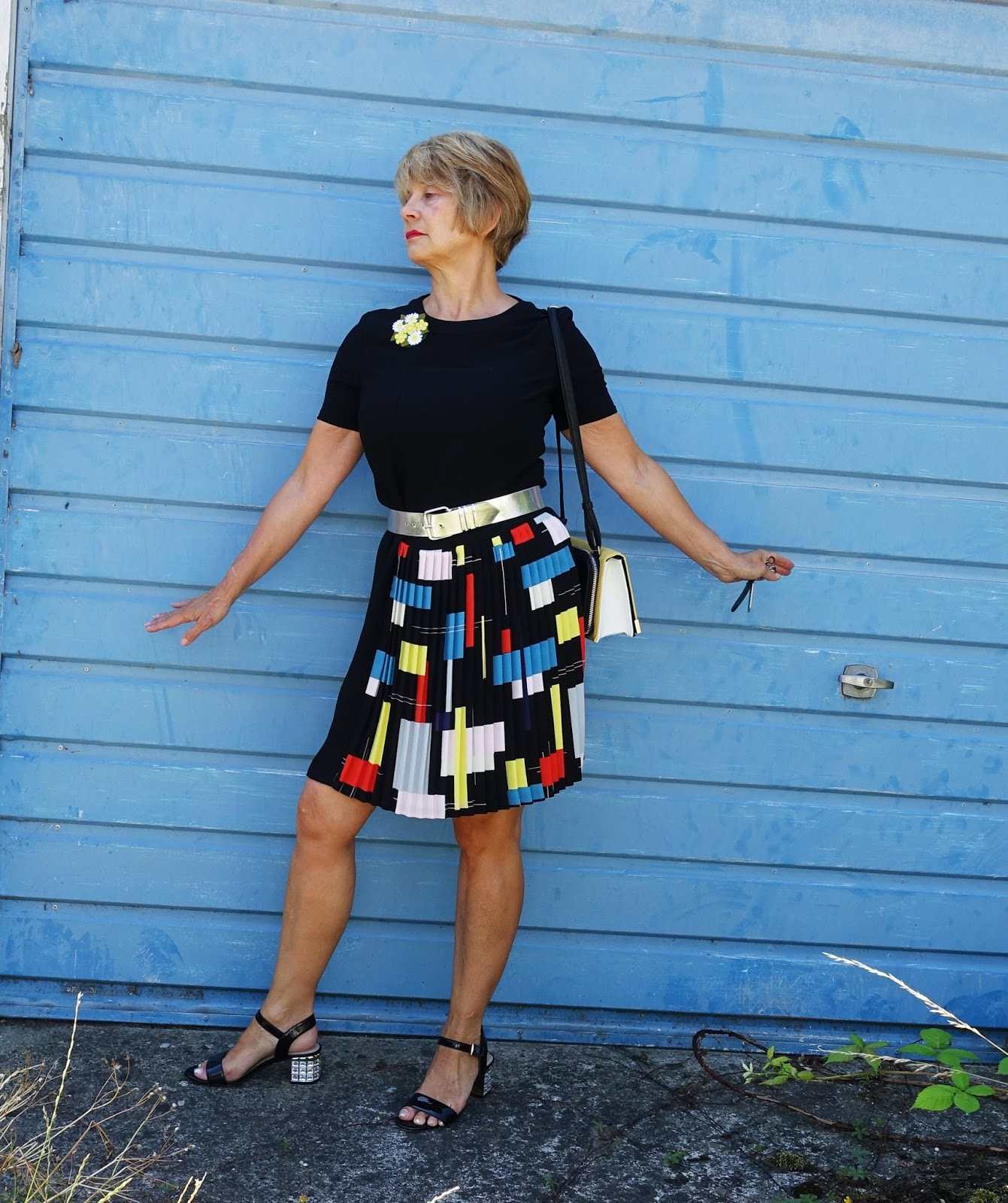 Gail Hanlon, blogger from Is This Mutton.com, adds yellow and silver accessories to a black panel pleat dress from Next to add some individuality for a cool workplace outfit.
