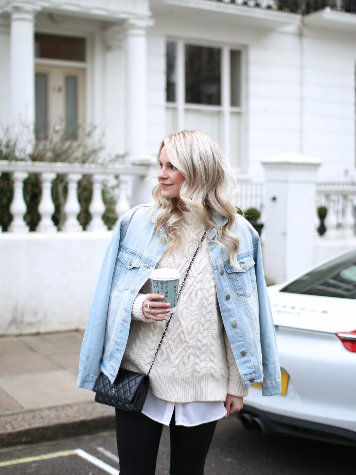 a blonde blogger wearing vintage style denim jacket and cable knit sweater in notting hill at sunset