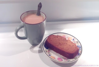 Photo of a cup of milky tea in a pale green mug with a spoon in it.  A slice of pumpkin loaf on a plate beside it.