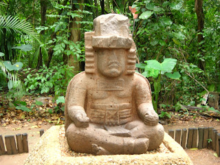 An Olmec stone statue depicting a man seated in a yogic posture called Sukhasana with his fingers in the Gyana Mudra position