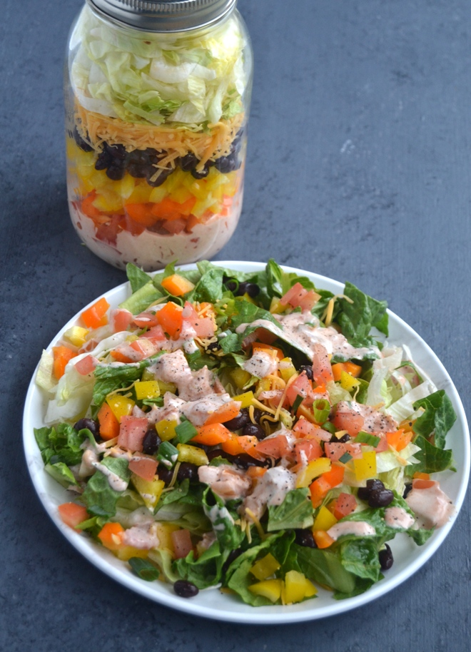 Mason Jar Taco Salads are easy to make and make the week ahead a breeze with having a nutritious lunch ready to go! Features layered lettuce, tomatoes, pepper, cheese, black beans and a creamy dressing. www.nutritionistreviews.com