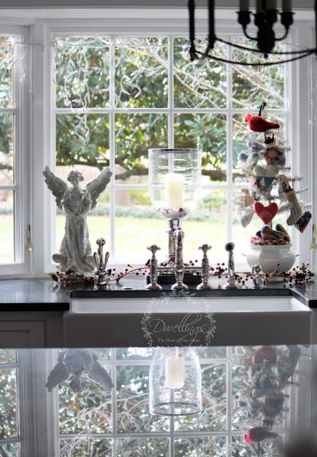 Kitchen window at Christmas with angels, candles and a tinsel tree decorated with homespun ornaments.