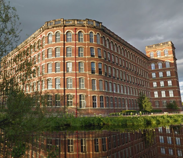 5-story red brick mill with white stone trim reflected in foreground pond
