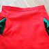 Roter Rock mit grünen Taschen