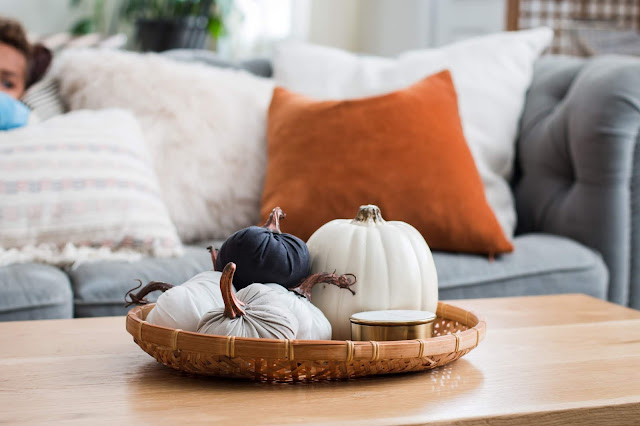 Pumpkins and a candle in a tray for simple fall decorating