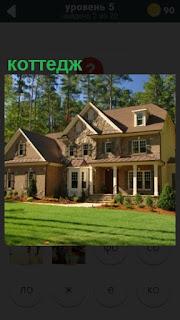построен коттедж и перед домом красивая зеленая лужайка