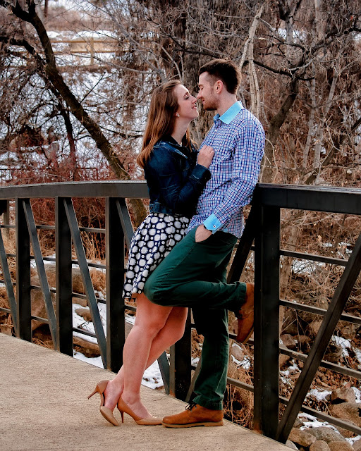 on a bridge at Eben G Fine Park a couple looks lovingly at one another for a photo during their engagement session