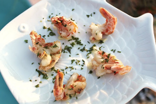 how to clean and cook rock shrimp these are on a white plate and butterflied with herb sauce