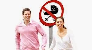 Una pareja de recien casados y un letrero de Prohibido tener bebé