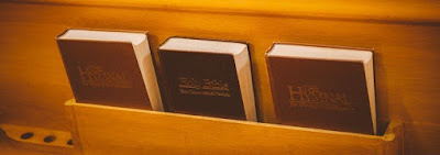 Back of a pew, with Bible and a hymnal on either side of it.