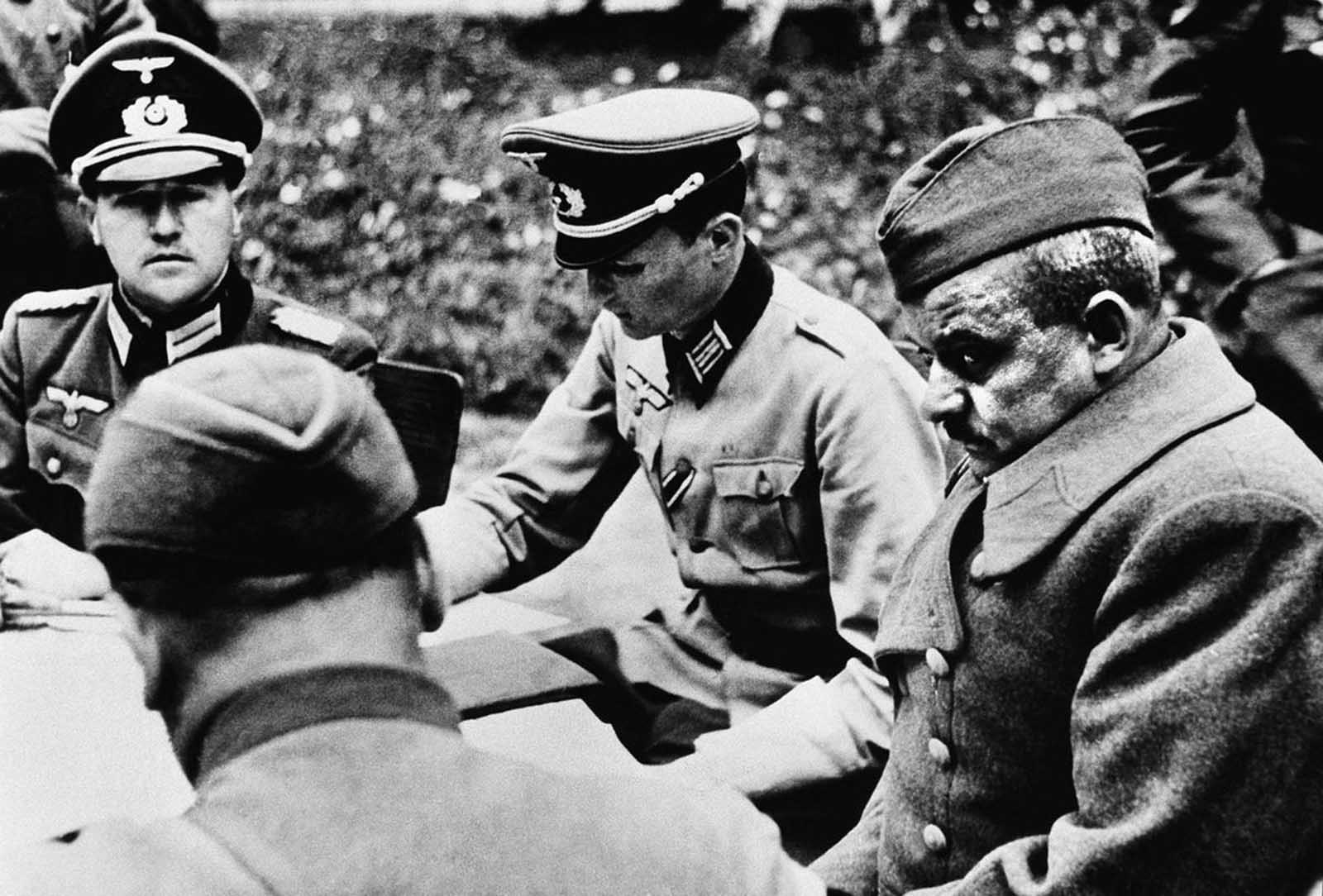 German sources described the gloomy looking officer at the right as a captured Russian colonel who is being interrogated by Nazi officers on October 24, 1941.