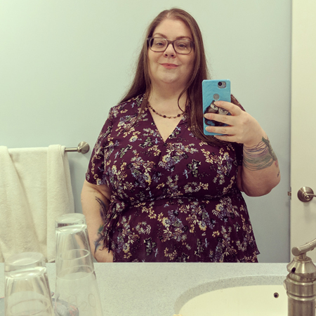 image of me standing in my bathroom mirror, seen from the waist up, with my hair down, wearing grey-framed glasses and a tie-waist burgundy blouse with a floral pattern