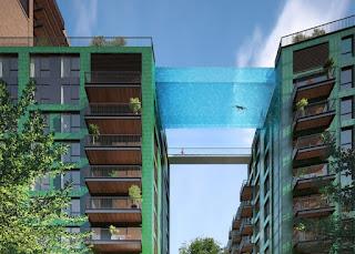 Foto de um projeto arquitetônico em Londres. Fachada de dois prédios residenciais, janelas envidraçadas e amplas sacadas. No décimo andar, entre os dois prédios , uma piscina de vidro suspensa com dimensões: 25 metros de comprimento, cinco metros de largura e três de profundidade. Ao fundo, no mesmo nivel da piscina, um transeunte caminha sobre a ponte cercada.