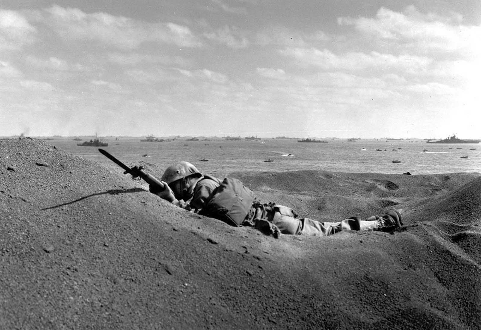 A U.S. Marine, killed by Japanese sniper fire, still holds his weapon as he lies in the black volcanic sand of Iwo Jima, on February 19, 1945, during the initial invasion on the island. In the background are the battleships of the U.S. fleet that made up the invasion task force.