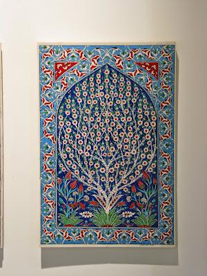 Peça grande de azulejo com cores fortes (azul escuro, vermelho, amarelo e azul claro) com tema de natureza