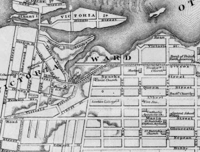 Crop of a map from 1874 which shows Ottawa with limits at Bank Street (East), Biddy Street (now Lisgar, South), Broad Street (in line with Rochester, West), and the Ottawa River (North), with street names, city wards, and prominent buildings labelled. A hashed line comes in from the east on Sparks Street, jogs north up Bank Street one block to Wellington, then continues west along Wellington and George, crossing Pooley's Bridge, turns northwest up Duke Street then north to Bridge Street where the line is shown stopping before Victoria, Albert, and Chaudière islands. Wellington Street and its extensions George St and Victoria Terrace, have a dotted line indicating the boundary between Victoria Ward (north of the line) and Wellington Ward (south of the line). Hillsides are indicated. Wellington Street is drawn at full width continuing west, beyond where George Street turns off it at a southwest angle, until the gorge that runs under Pooley's Bridge a little further south.