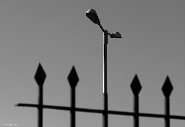 A Black and White Minimalist Photo of a Street Lamp as seen through an Iron Spade Shapes Broken Metal Fence.