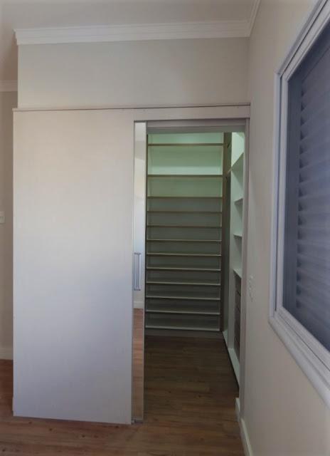 Na suíte principal, uma porta de correr fecha discretamente o closet, que apesar de ocupar pouco espaço, oferece distribuição interna suficiente para guardar os pertences do casal.