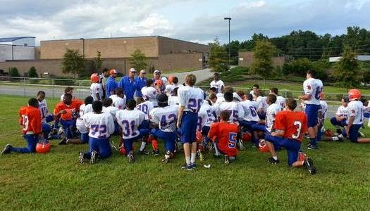 jugadores oran en el campo de escuela