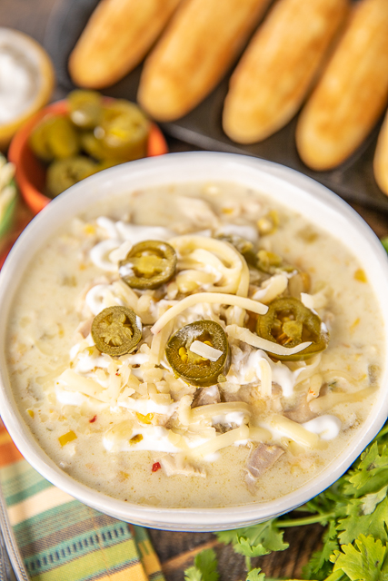 Chicken & Corn Chowder - crazy delicious and ready in 30 minutes! Chicken, onion, garlic, cumin, chicken broth, half-and-half, pepper jack cheese, corn kernels, creamed corn and green chiles. I wanted to lick the bowl! Great for a crowd. Top the chowder with some sour cream, jalapeños and extra cheese. All you need is some cornbread and you are set! The BEST!! #chicken #soup #chickensoup