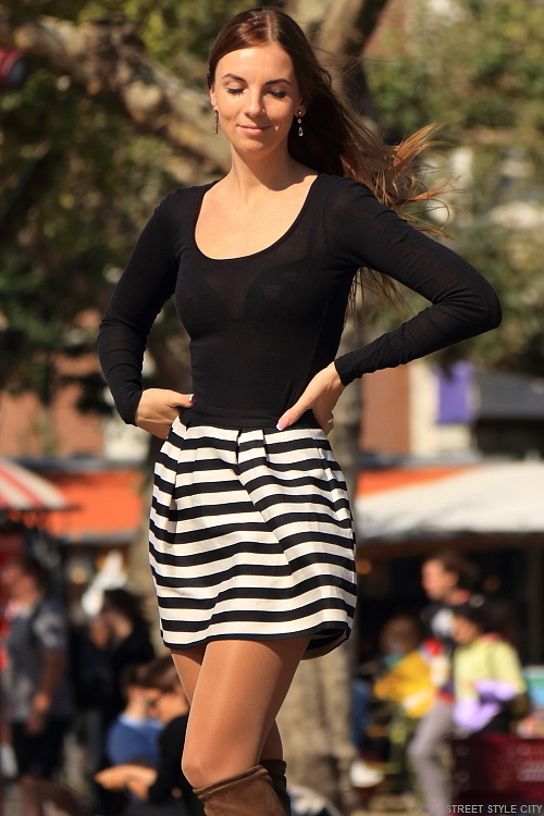 Dutch girl wearing seethrough top, striped miniskirt, pantyhose and long boots in the streets of amsterdam during fashion week. Street style fashion look outfit ootd candi woman girl sexy