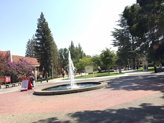 A two floor building built of brick stands at the end of a long paved walkway lined with lawns and tall trees. In the foreground is a fountain of water.