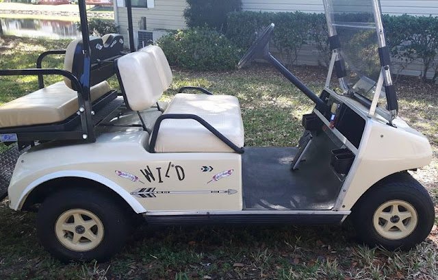 "A club-car golf cart with ""wild"" on the side."