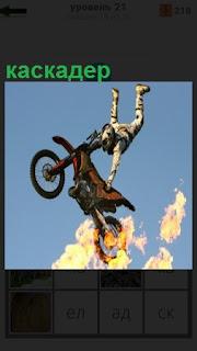 Мужчина каскадер выполняет трюк на мотоцикле с огнем на колесе
