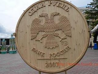 Moneda gigante tallada en madera.