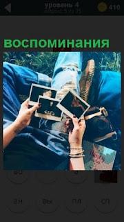 На коленях и в руках мужчины находятся фотографии, воспоминания о прошлом