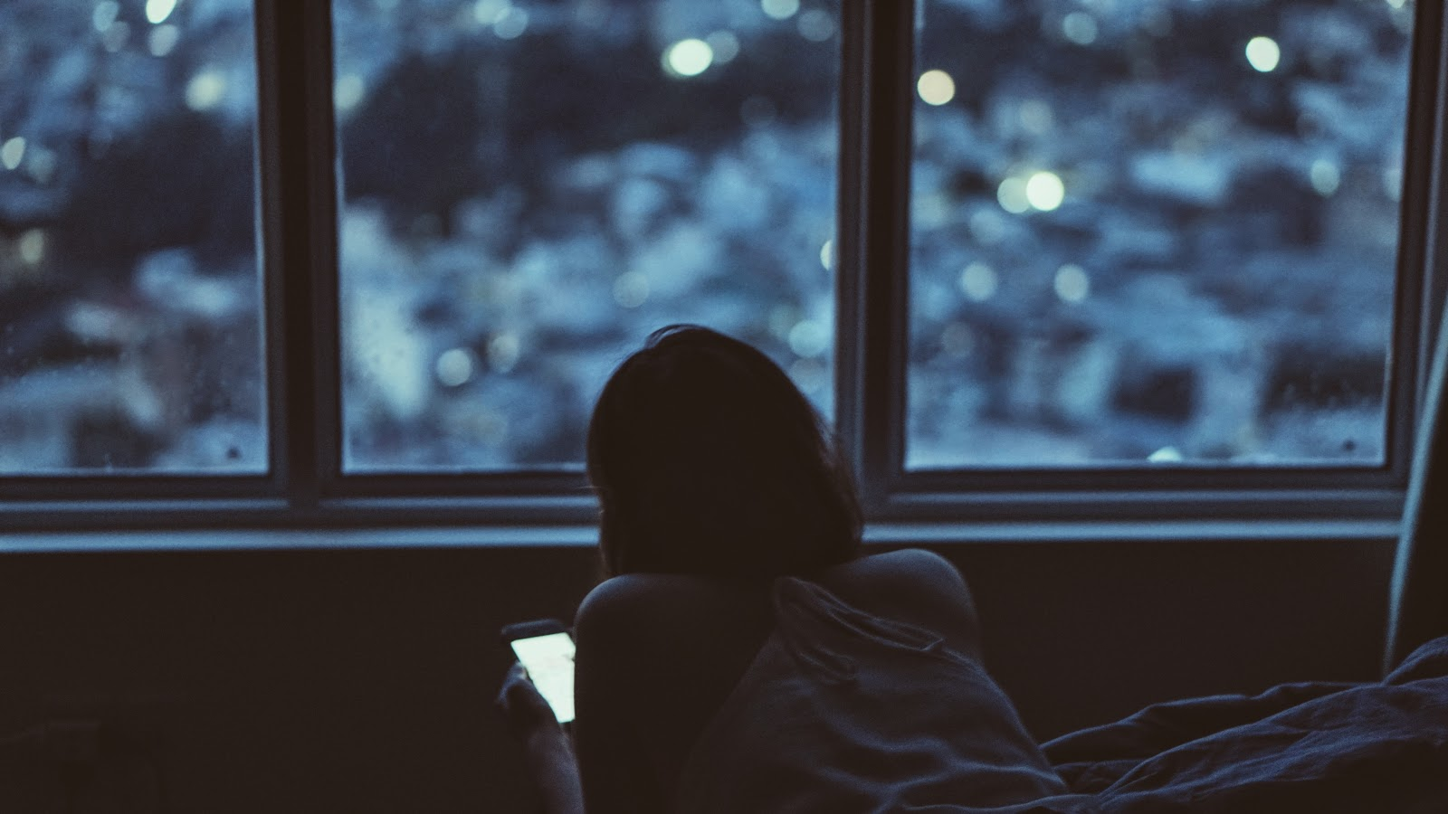 夜の暗い部屋でスマホを使っている少女