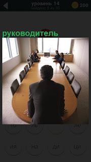 Длинный стол, во главе которого стоит руководитель перед сотрудниками