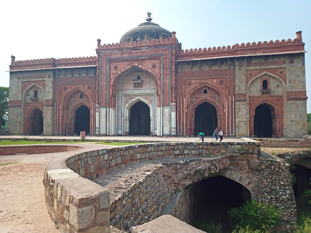 Monumental sandstone mosque with domed roof and five decorated entry archways at Purana Qila