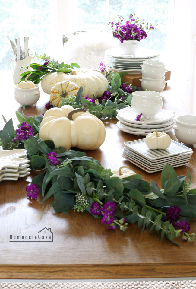 Greenery, white pumpkins and purple flowers
