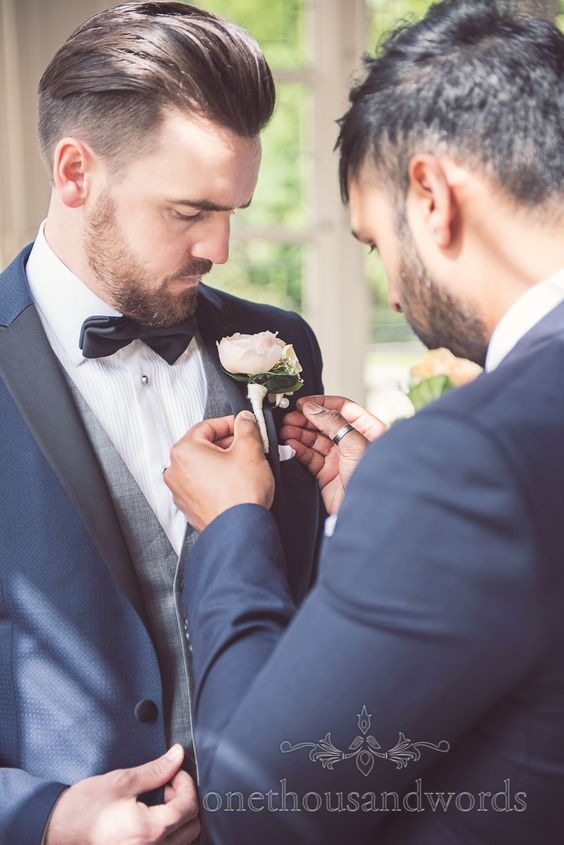 Groom in Bow Tie has button hole added by Best Man at Highcliffe Castle.