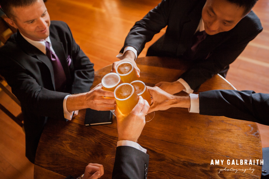 groomsmen clinking glasses of beer