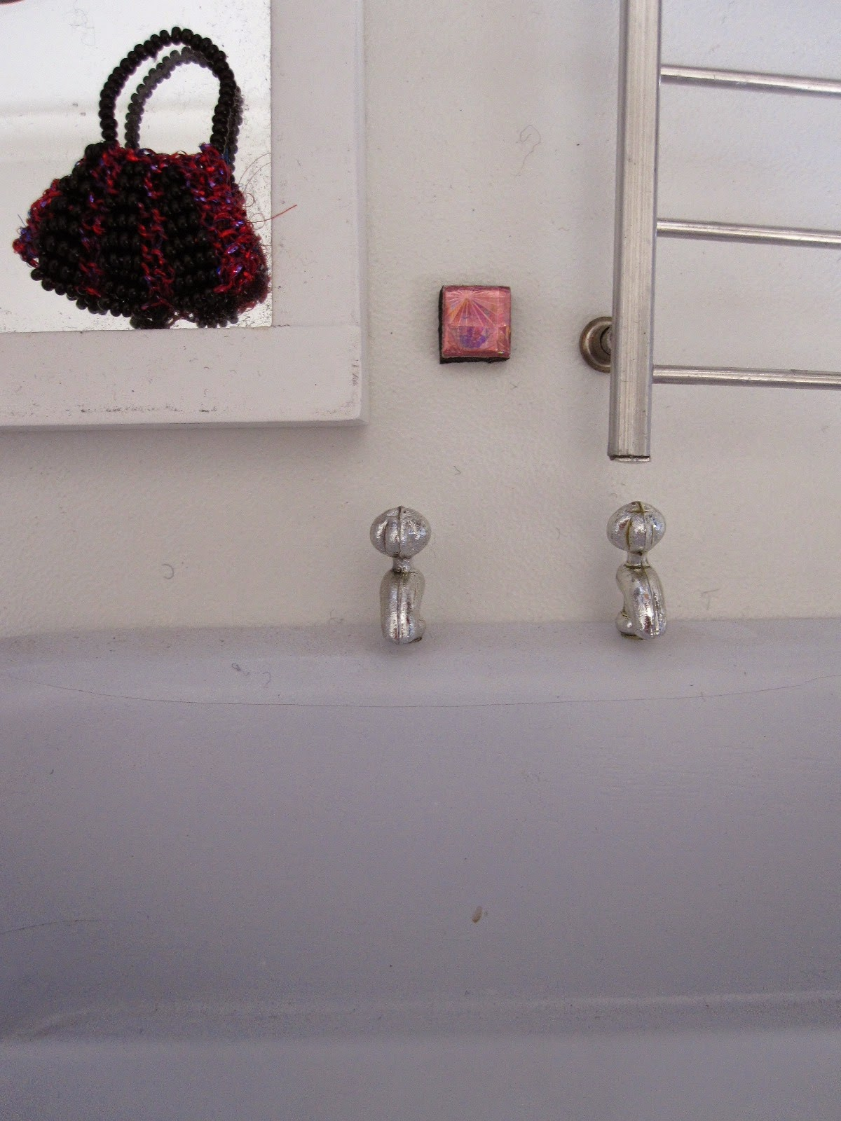 Dolls house miniature bath, mirror and heated towel rail. On the mirror is a beaded bag and on the wall is a tiny pinky-silver tile.