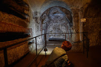 "A visitor looks at a fresco, part of the restored ""dei Fornai"" (bakers) cubicle, during a visit after the restoration of the catacomb of Santa Domitilla, in central Rome, on May 30, 2017 [Credit: AFP/Andreas Solaro]"
