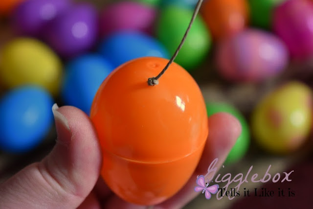 simple and cheap Easter decoration made with a gift bag plastic eggs and string, Easter decoration, cheap Easter decoration, using plastic Easter eggs for more than just egg hunts and baskets,