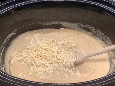 Cooked cauliflower soup in a slow cooker with grated smoked cheese on top