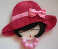 rosto de daminha em feltro com chapéu e laço