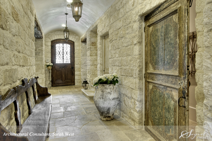 18th century rustic wood antique door from Chateau Domingue in a home with stone walls and large French pots.