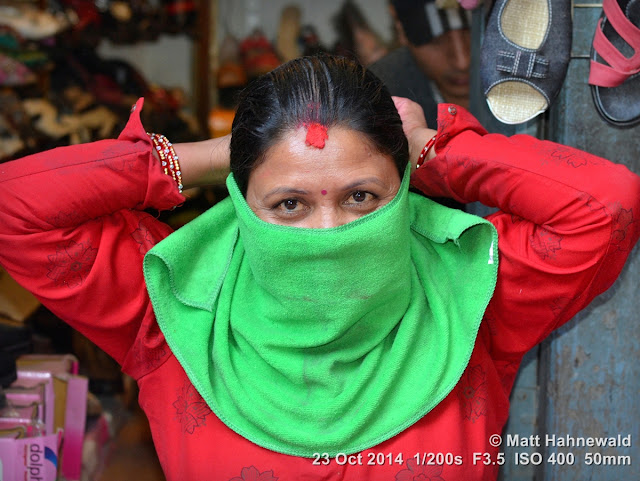 people, street portrait, headshot, face, eyes, eye contact, Hindu saleslady, face bandana, pollution, Nepal, Kathmandu