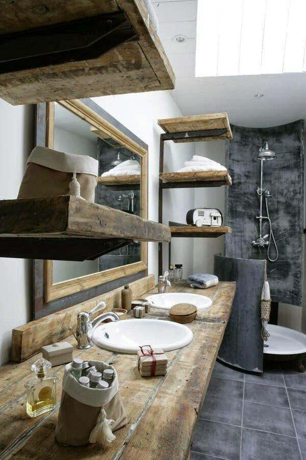las estanteras de hierro forjado y las repisas de madera antigua dan un aspecto rstico a este cuarto de bao