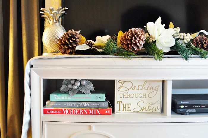 A TV stand can function as a mantel for holiday decor. An eclectic holiday tour of a small apartment living and dining space decorated for Christmas! The black, white, gold and silver touches are gorgeous.
